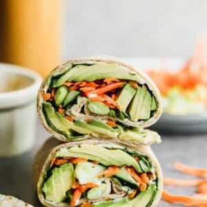 Two veggie wraps stacked on each other, filled with avocado, carrots, hummus and edamame.