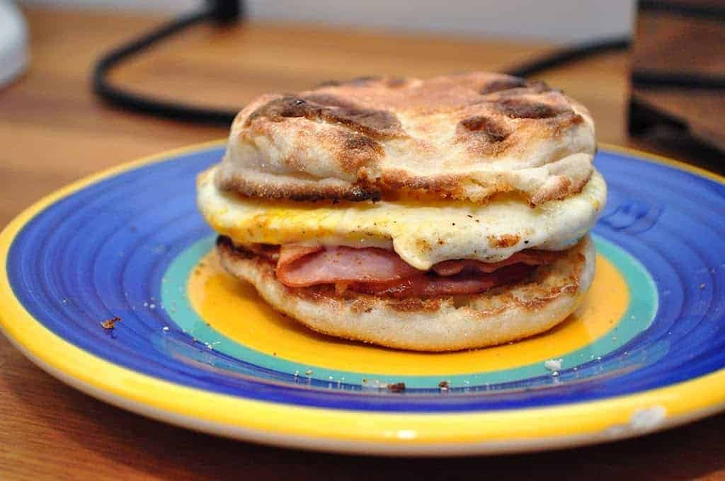 A ham and egg breakfast sandwich sitting on a plate.
