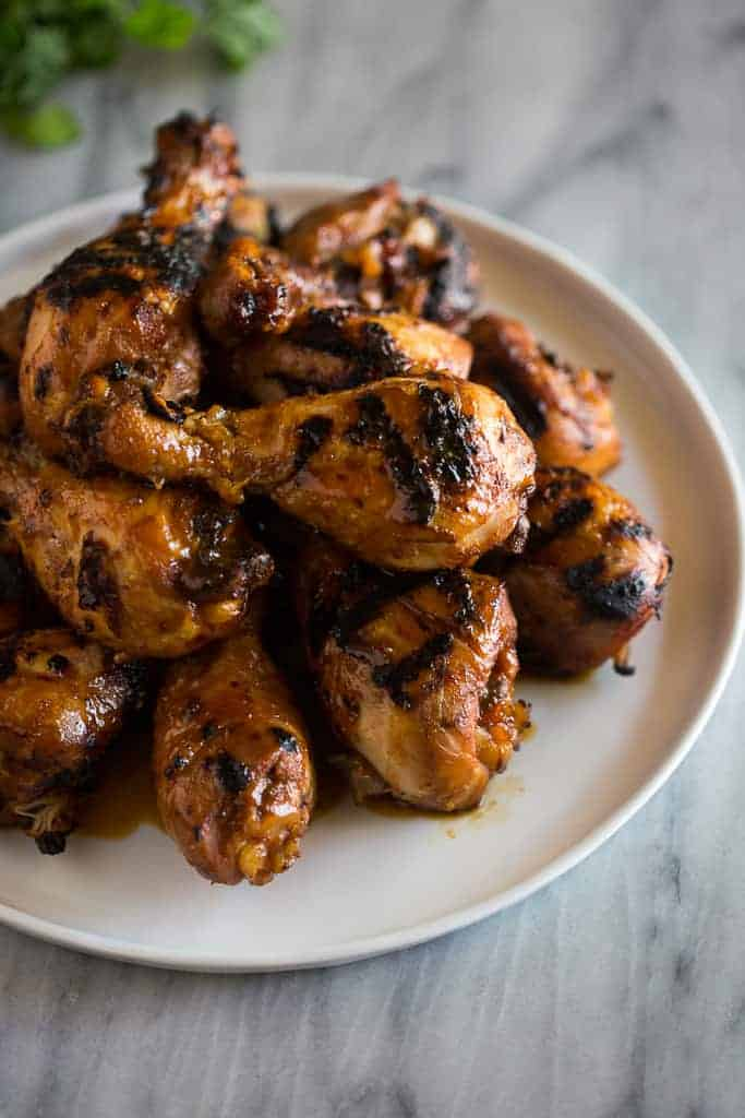 BBQ chicken drumsticks stacked into a pile on a white plate.