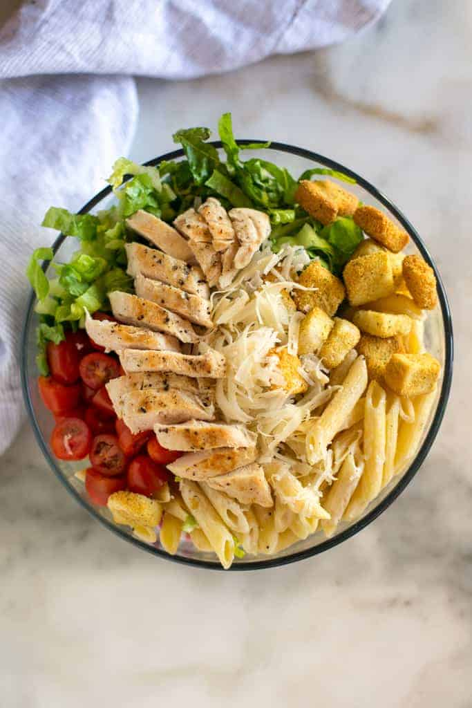 A bowl full of the ingredients to make chicken caesar pasta salad, including cooked penne pasta, chicken, tomatoes, croutons, lettuce and parmesan cheese.