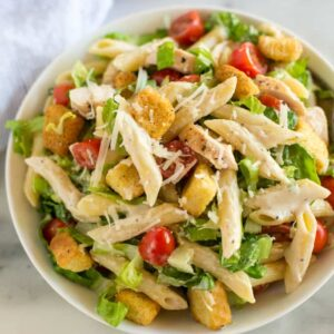 A serving bowl full of chicken caesar pasta salad with a dish towel in the background.