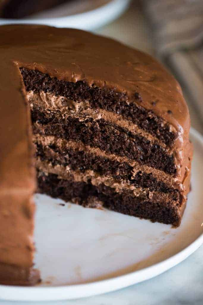 A four layer chocolate cake with a large slice of chocolate cake removed from it, showing the layers of chocolate mousse filling between each layer.
