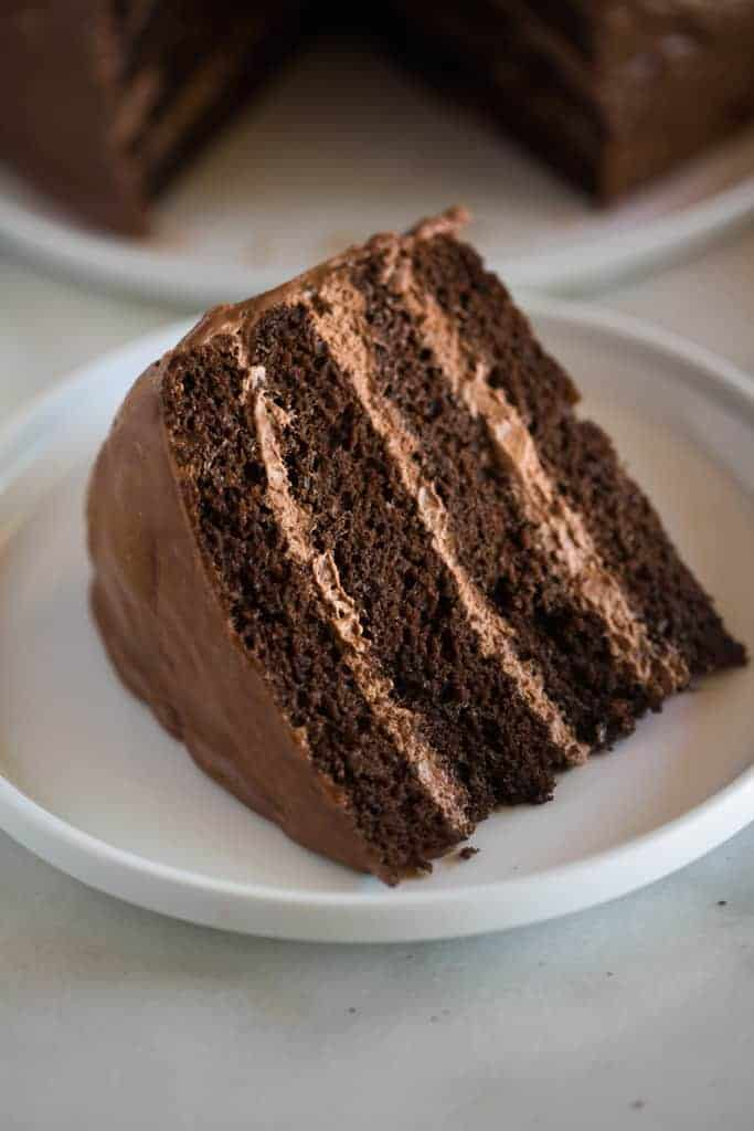 A slice of homemade chocolate cake with layers of chocolate mousse filling, on a white plate with the remaining full chocolate cake in the background.