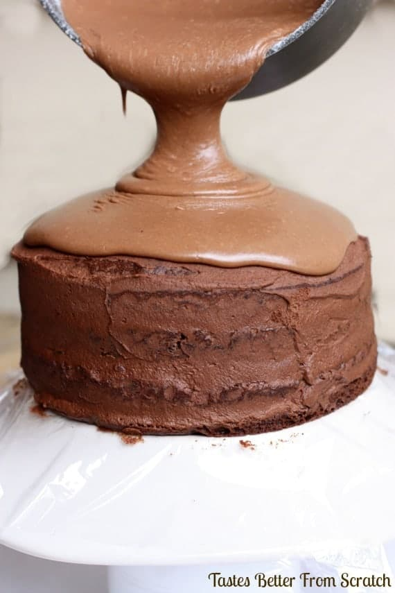 A four layer chocolate mousse cake sitting on a white cake platter with chocolate ganache being poured over the top.