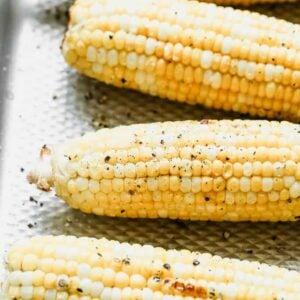 Grilled corn ears on a baking sheet.
