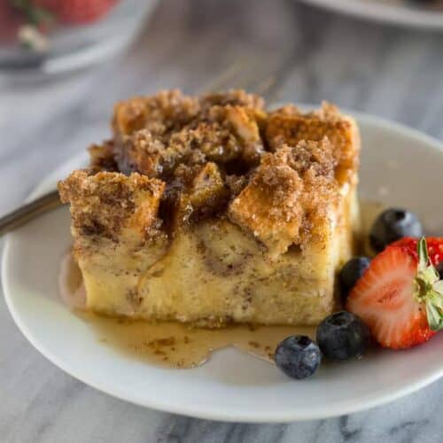 A slice of baked french toast casserole served on a white plate with syrup and berries.