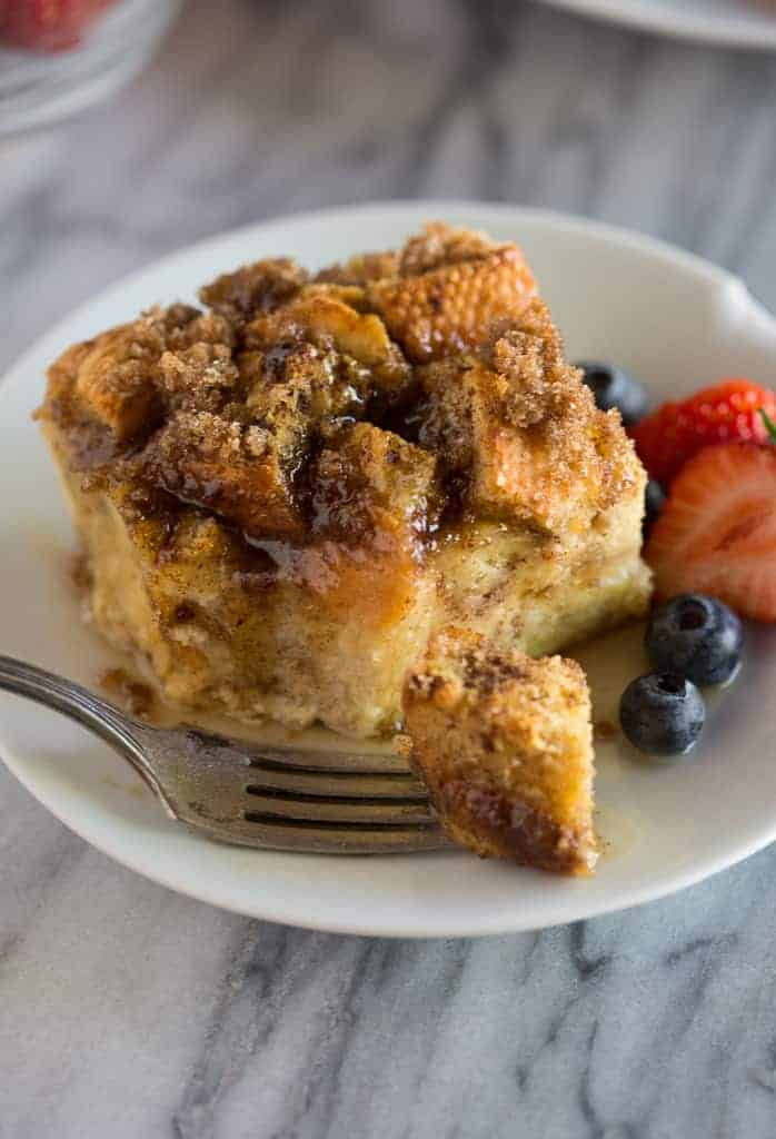 A slice of baked french toast served on a plate with berries and a fork.