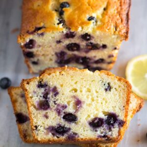 Stacked slices of lemon blueberry bread with the loaf of quick bread behind it.