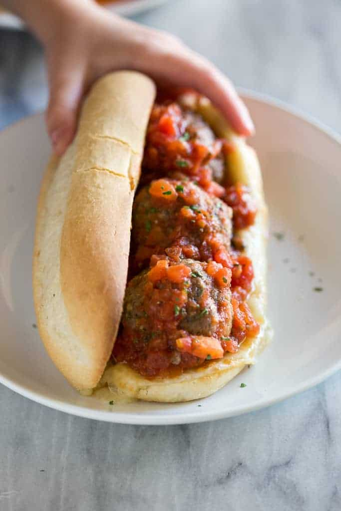 A meatball sub on a white plate with a hand holding the back of it.