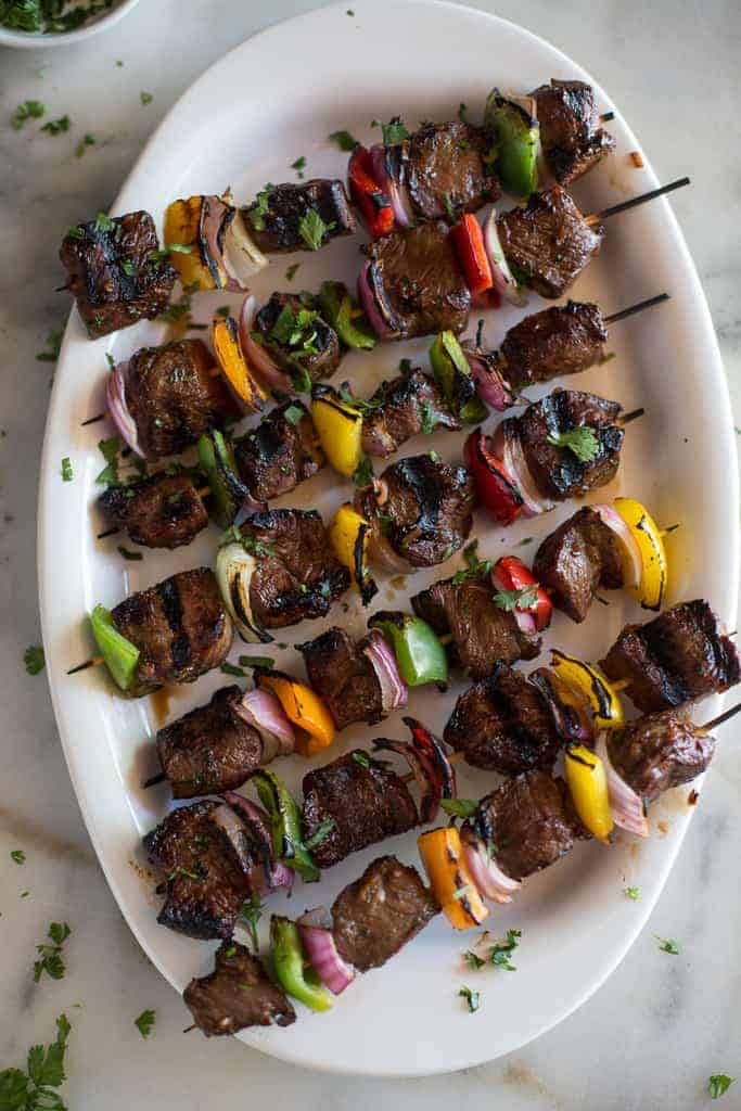 Steak kebabs with bell peppers and onion lined at an angle on a white platter.