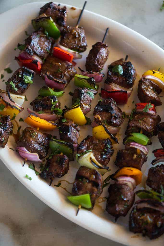 Steak Kebabs on wooden skewers with bell pepper and onion, served in a line on a white plate.