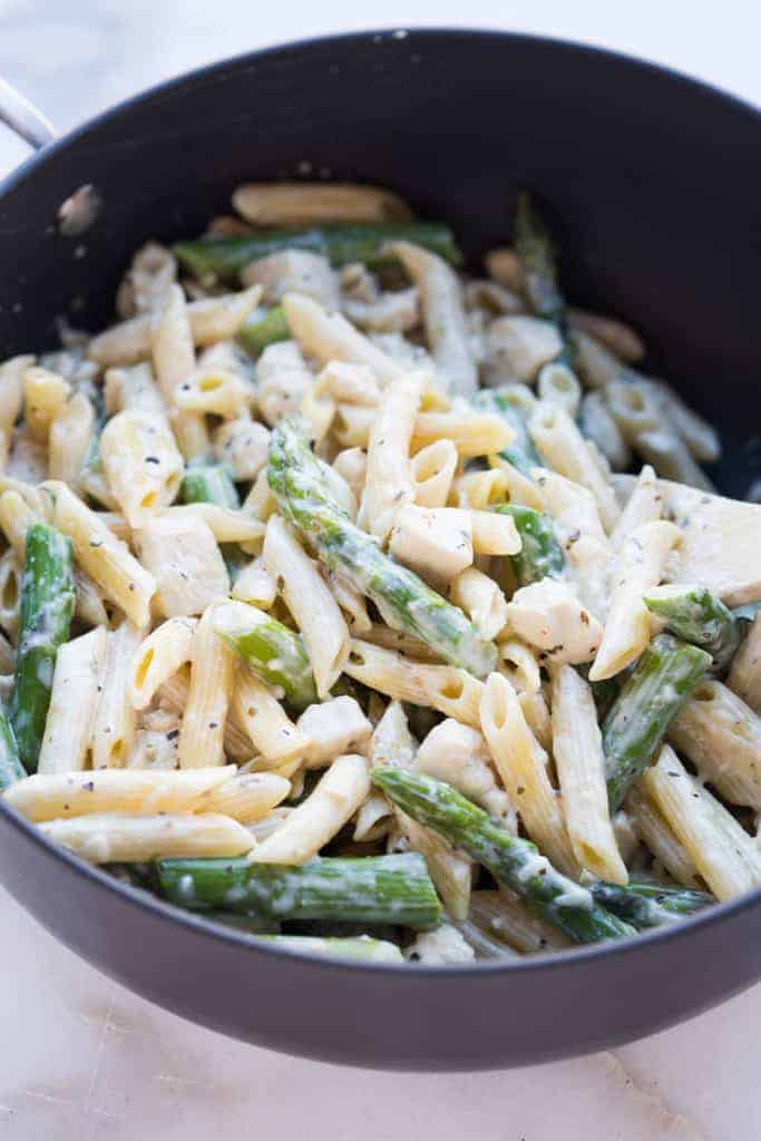 Skillet filled with creamy chicken and asparagus pasta.