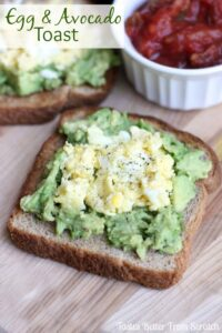 A slice of bread topped with smashed avocado, scrambled eggs, and salt and pepper.