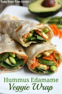 Three hummus edamame veggie wraps stacked in a pile and filled with spinach, carrots, edamame, and avocado.