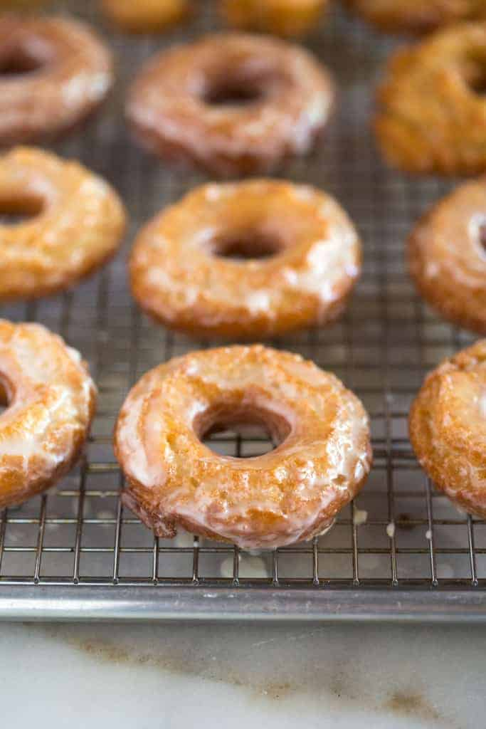 Homemade sour cream donuts with glaze resting on a wire cooling rack on top of a baking sheet.