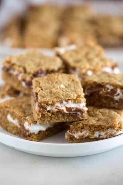 A plate full of s'more cookies bars with layers of graham cracker cookie, and chocolate and marshmallow in the middle.