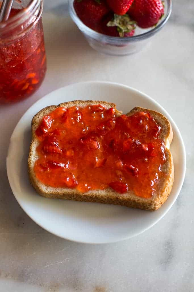 Slice of bread with strawberry jam on a small white plate. Jam jar and fresh strawberries in the background.