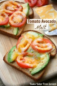 A slice of wheat toast topped with thins slices of avocados, sliced tomatoes, and cheese that has been broiled in the oven.