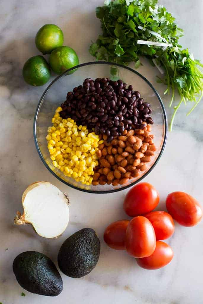 The ingredients needed to make cowboy caviar including a bowl with black beans, corn, pinto beans, and tomatoes, avocados, onion, lime and cilantro placed around the bowl.