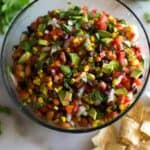 Cowboy Caviar served in a big glass bowl with chips, cilantro and a halved lime on the sides.