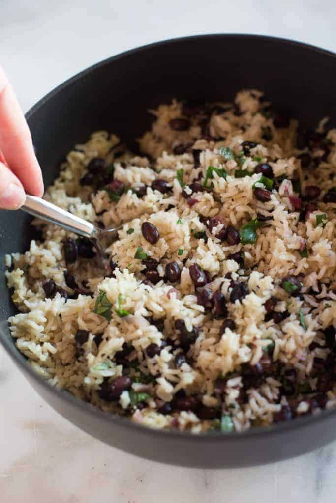 A saute pan filled with cilantro lime rice and black beans.
