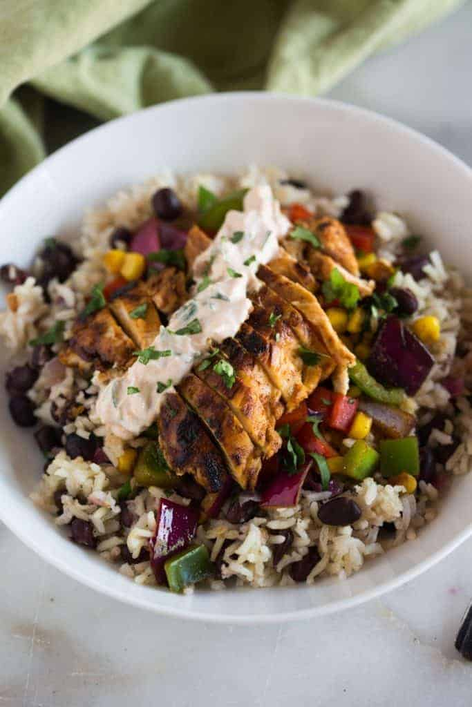 A white bowl filled with cilantro lime rice with black beans and topped with marinated and grilled chicken and a chipotle cream sauce, sprinkled with fresh cilantro and a green dish towel in the background.