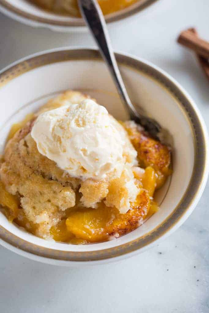 Peach cobbler served with a scoop of vanilla ice cream on top, in a bowl with a spoon.