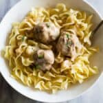 Three Swedish Meatballs and gravy served over egg noodles in a white bowl with a fork.