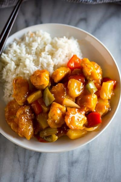A white plate with homemade sweet and sour chicken and white rice, and chopsticks resting on the plate.