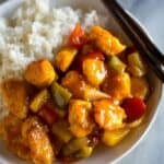Close-up photo of a plate with sweet and sour chicken and white rice.