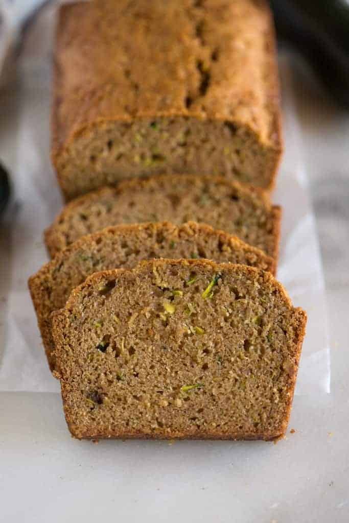 Slices of freshly baked zucchini bread stacked up against the remaining un-cut loaf of bread.