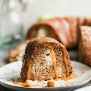 A slice of Apple Bundt Cake on a plate with caramel sauce on top.