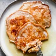 Three apple pancakes on a plate with a fork taking a bite.