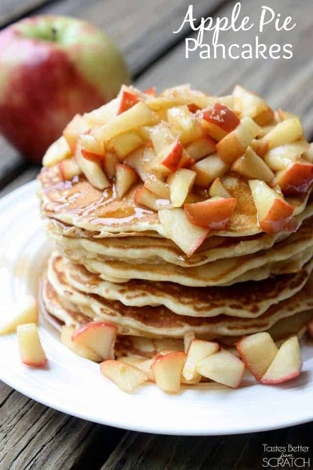A huge stack of Apple Pie Pancakes topped with diced apples and maple syrup.