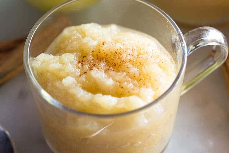 A clear glass cup with a handle filled with homemade applesauce with apples, cinnamon sticks and another cup of applesauce in the background.