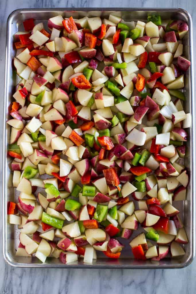 A sheet pan with the ingredients for baking breakfast potatoes including chopped potatoes, bell pepper and onion.