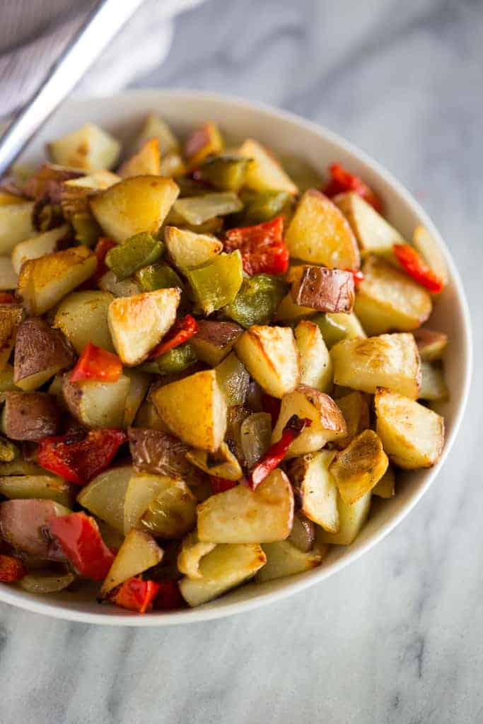 Breakfast potatoes with green and red bell peppers served in a white bowl.