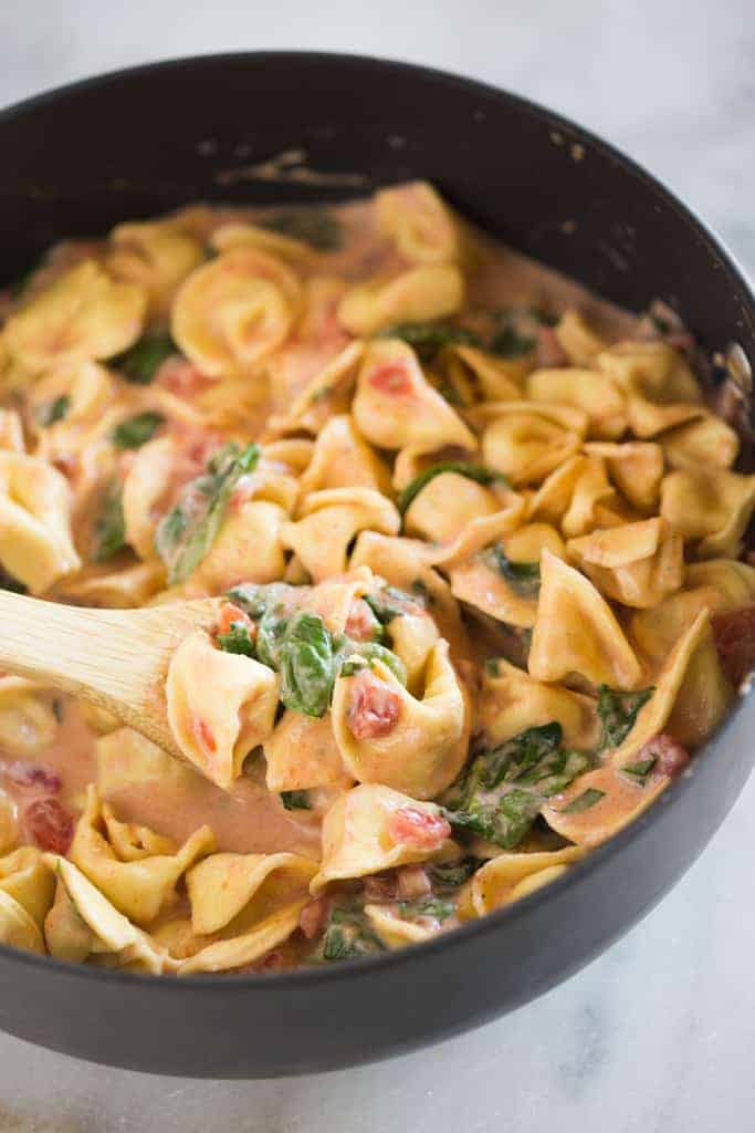 A saucepan with cheese tortellini in a creamy pink sauce with tomatoes, spinach and basil.