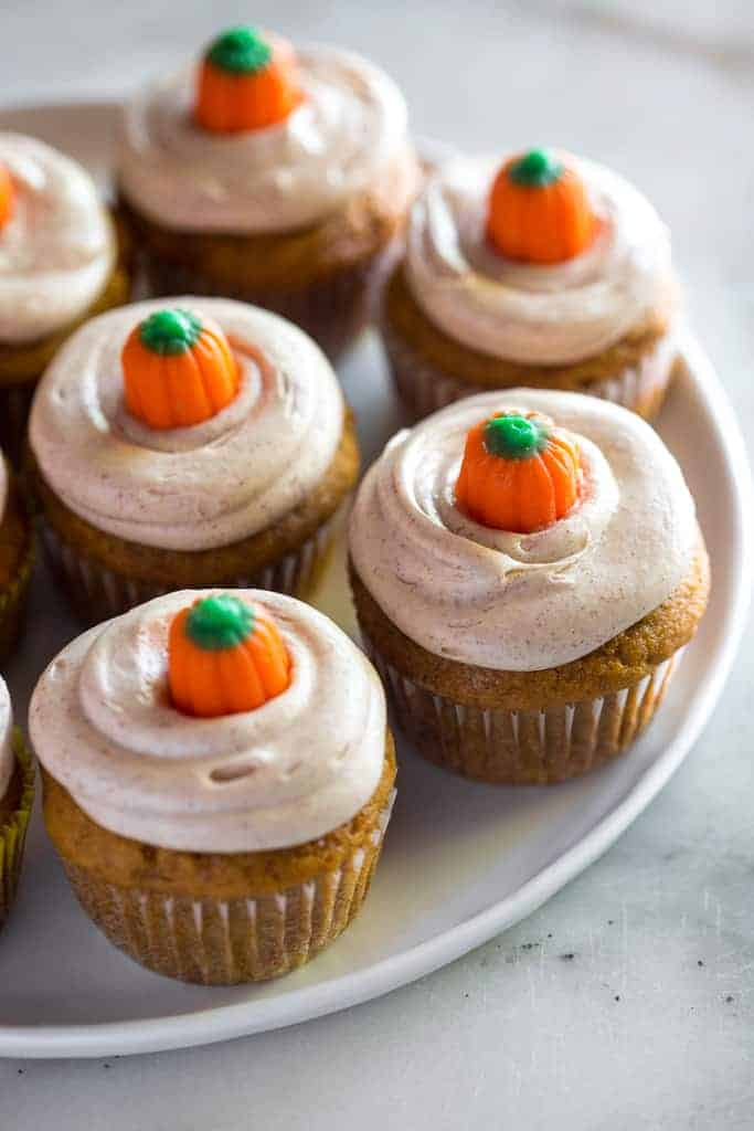 A white plate with frosted pumpkin cupcakes on it.