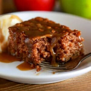 Apple cake made with fresh grated apples, served with caramel sauce drizzled on top and a scoop of ice cream on side.