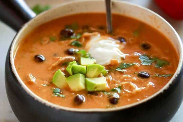 A black soup bowl with a handle, full of chicken enchilada soup with black beans and topped with diced avocado and sour cream.