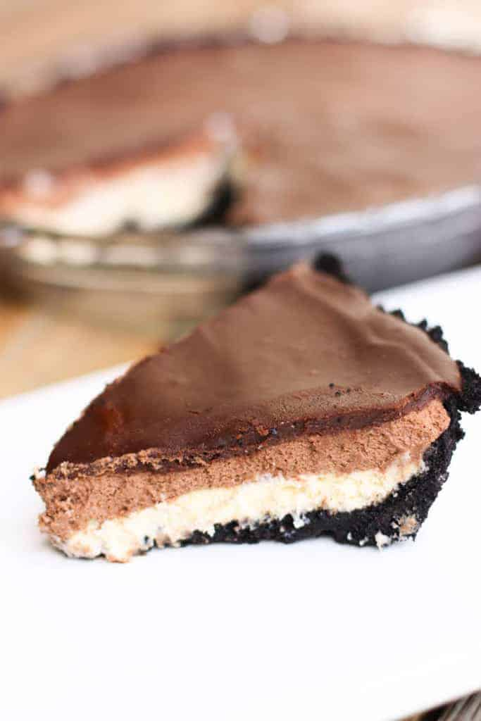 Chocolate mousse cheesecake with an oreo crust, a cheesecake layer topped with chocolate mousse and chocolate ganache.