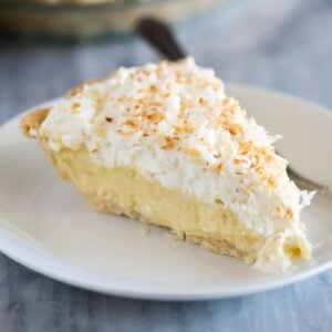 A slice of coconut cream pie on a white plate with a fork.