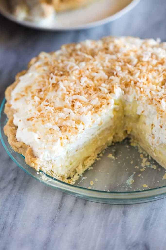 A whole homemade coconut cream pie with one slice removed.