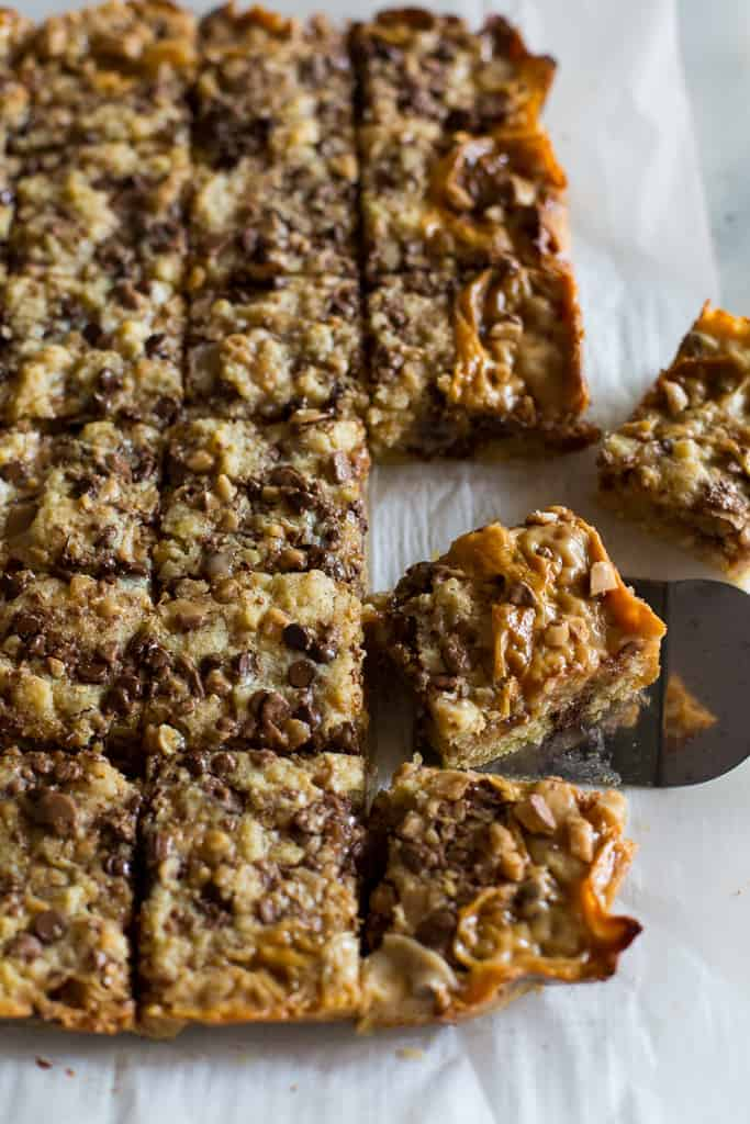 Cookie bars cut into squares and a metal spatula picking one up.
