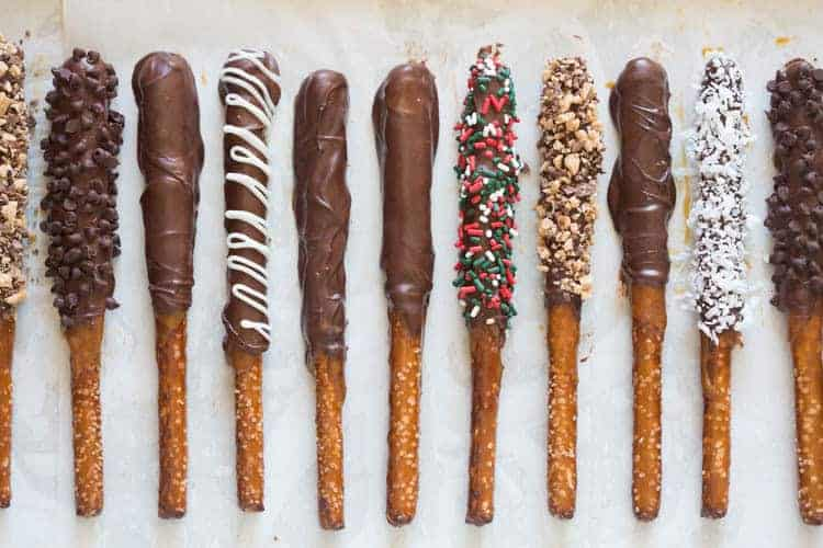 Overhead view of different kinds of homemade dipped pretzel rods with chocolate caramel, white chocolate, sprinkles, coconut, and crushed heath bars.