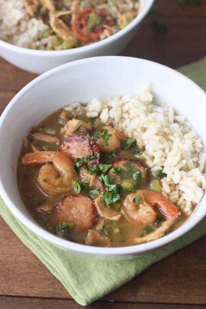 A bowl filled with Authentic New Orleans Style Gumbo and white rice.