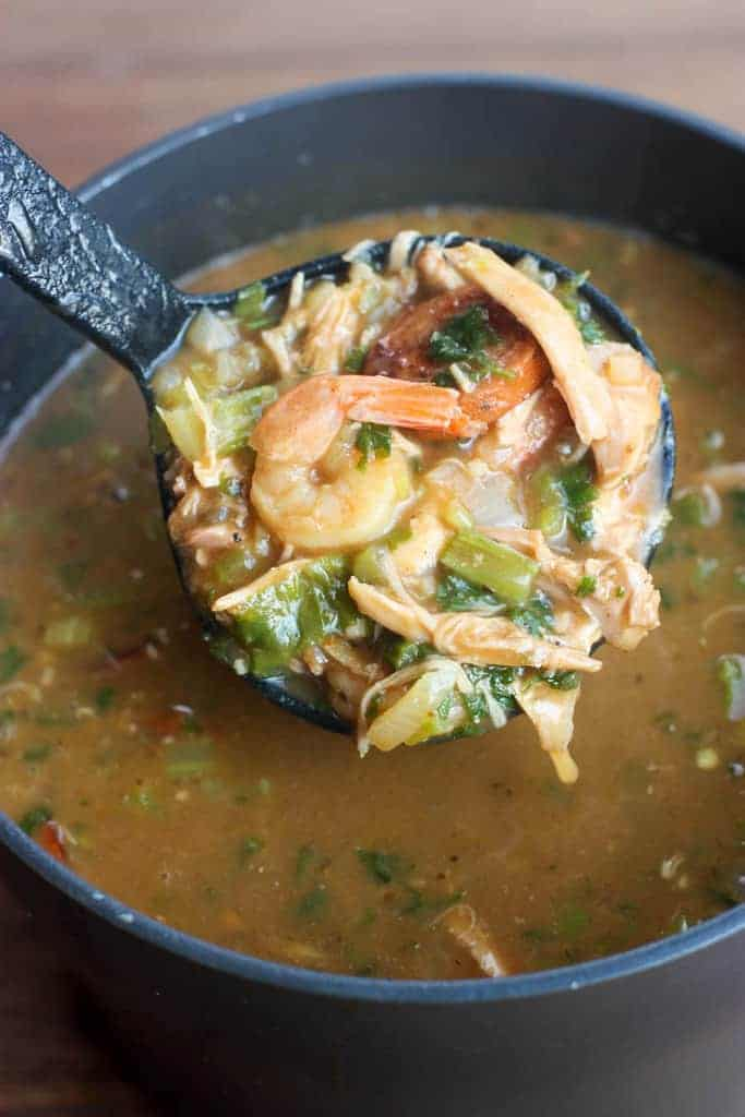 A large pot filled with a New Orleans Style Gumbo soup mixture and a ladle holding a scoop of the gumbo.