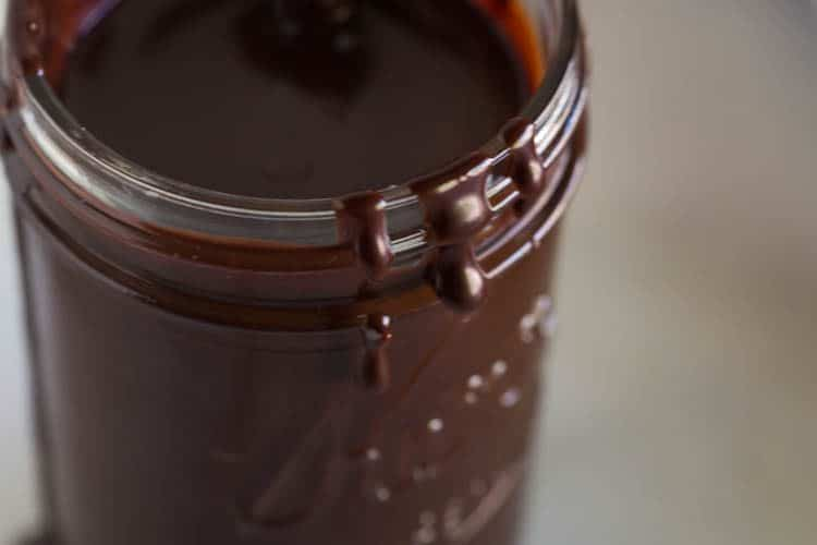 A glass mason jar filled with hot fudge sauce and a spoon in it.