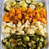 Roasted Vegetables on a white tray including butternut squash, brussels sprouts, cauliflower, and zucchini.